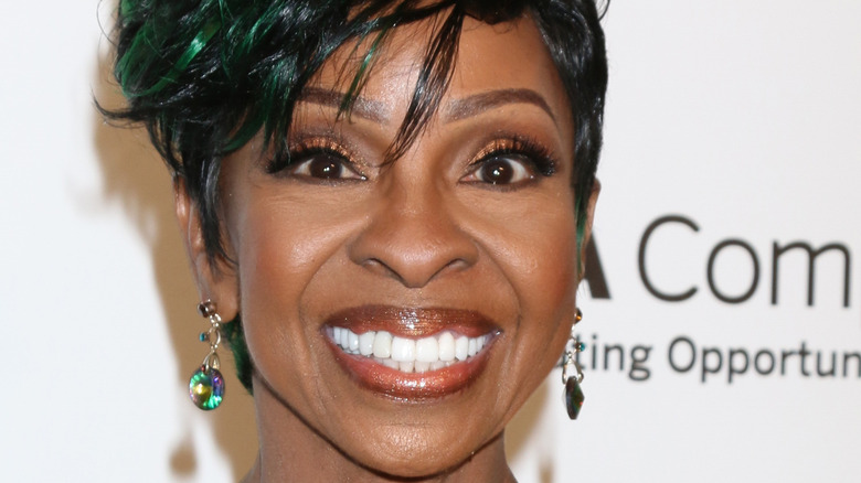 Gladys Knight smiling widely on a red carpet