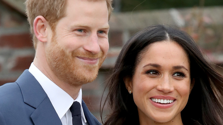Prince Harry and Meghan Markle smiling at an event