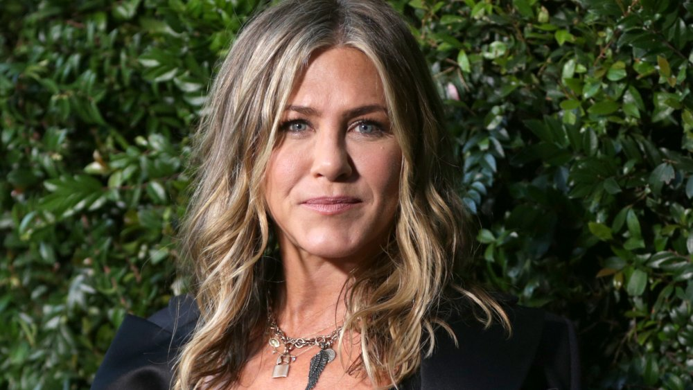 Jennifer Aniston standing in front of a hedge