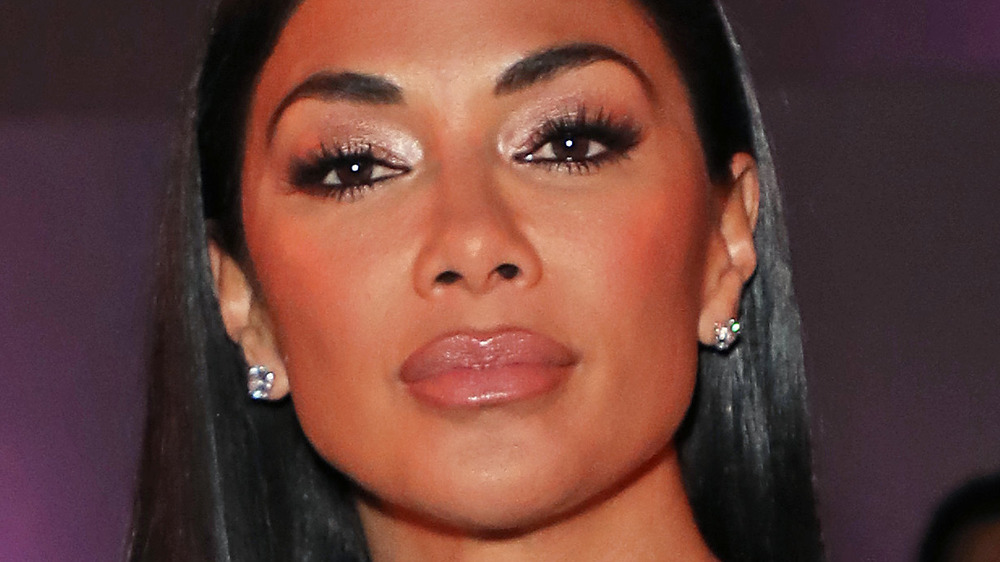 Nicole Scherzinger wears diamond earrings and glossy lipstick.