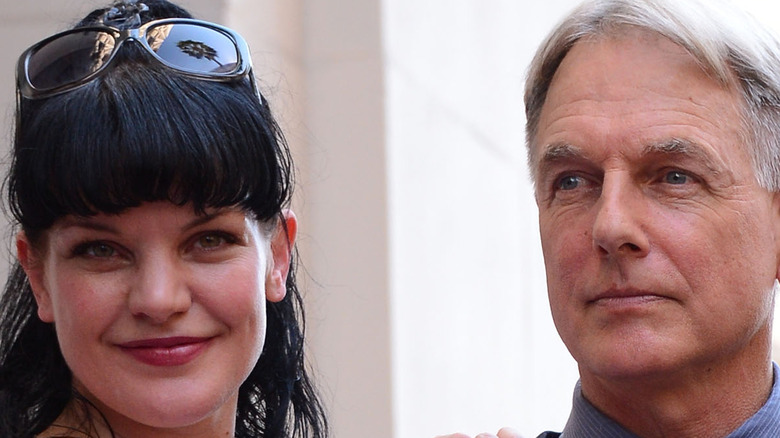 Pauley Perrette puts her arm on Mark Harmon and smiles.