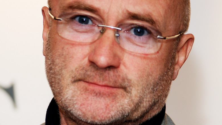 Phil Collins poses at an event.