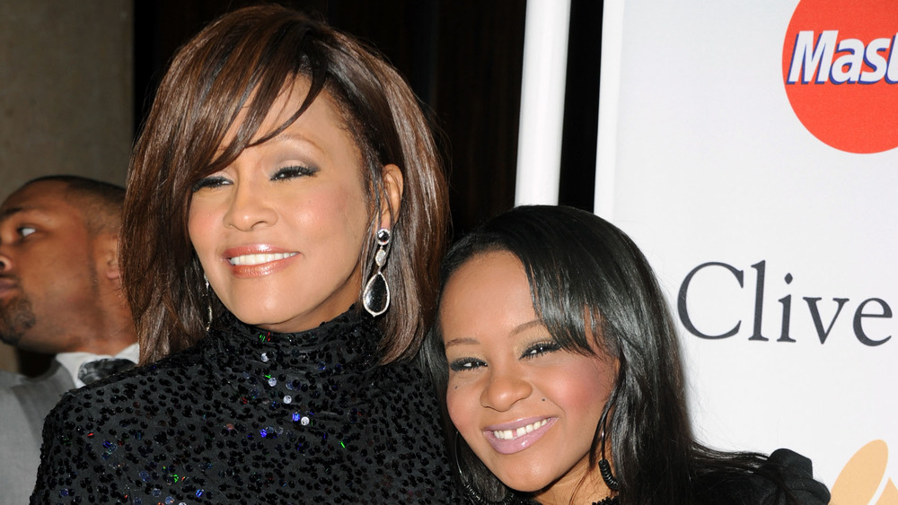 Whitney Houston poses at an event with daughter Bobbi Kristina Brown