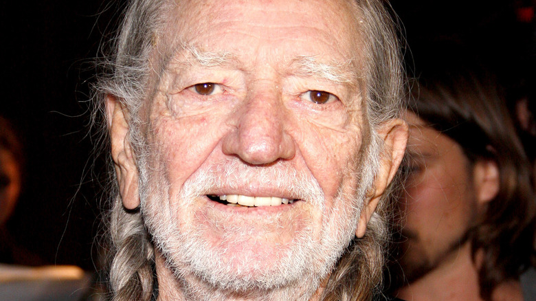 Willie Nelson smiling with braids