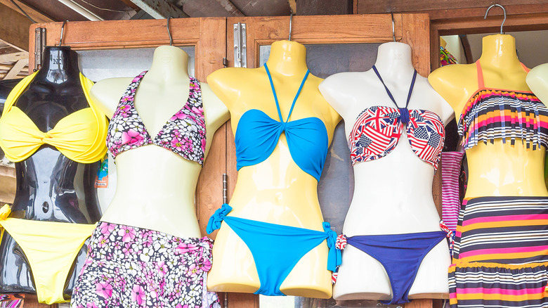 Mannequins wearing colorful bikinis at a store