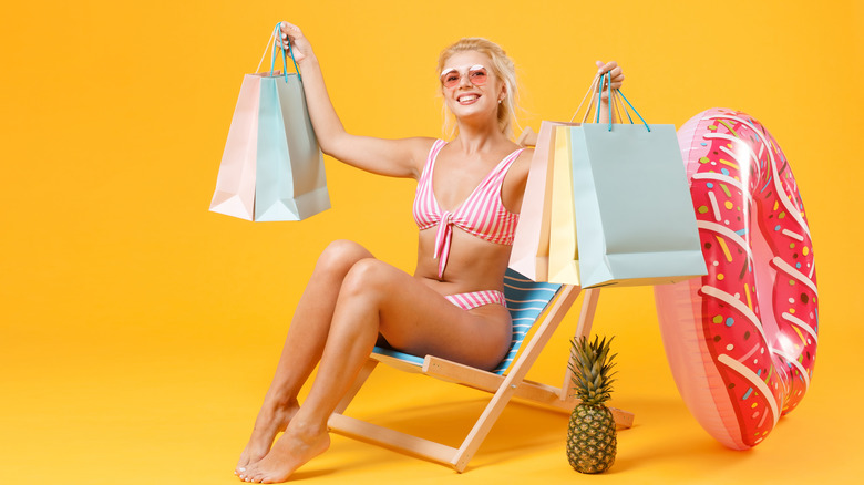 woman in a striped bathing suit holding shopping bags