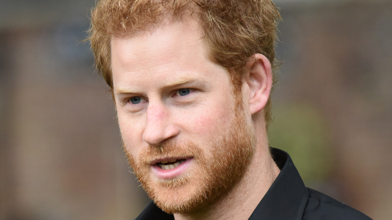 Prince Harry wears a black shirt at an event.