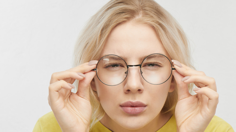 A woman squinting in glasses