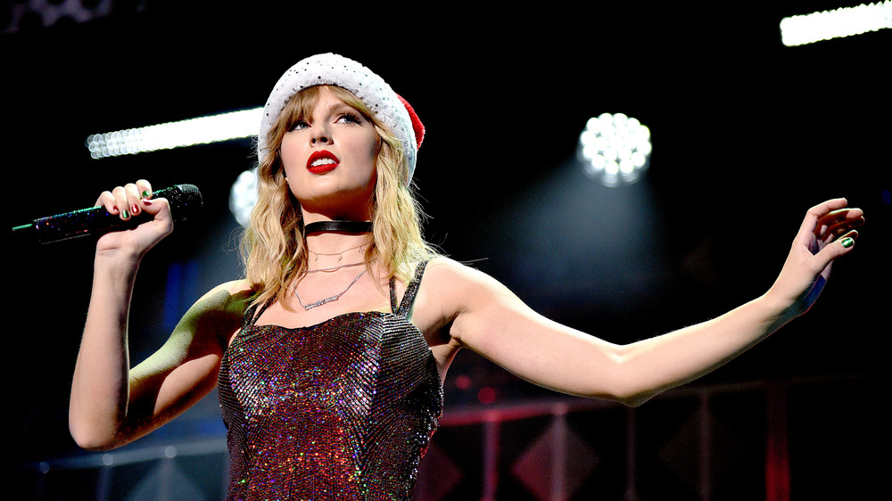 Taylor Swift performing in a Santa hat