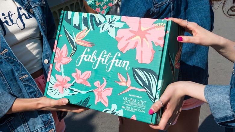 Multiple hands holding FabFitFun box