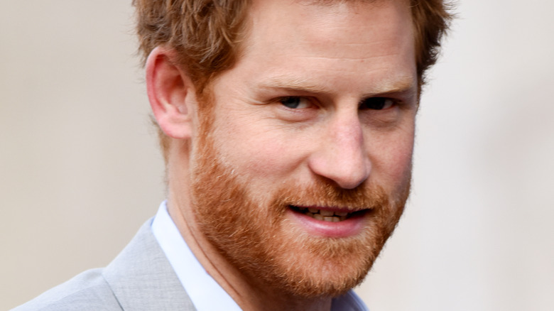 Prince Harry wears a gray suit.