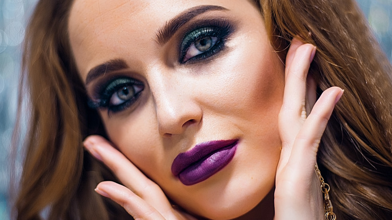 Woman with crimped hair wearing dramatic eye makeup and lipstick touching her face and  tilting her head to the side.