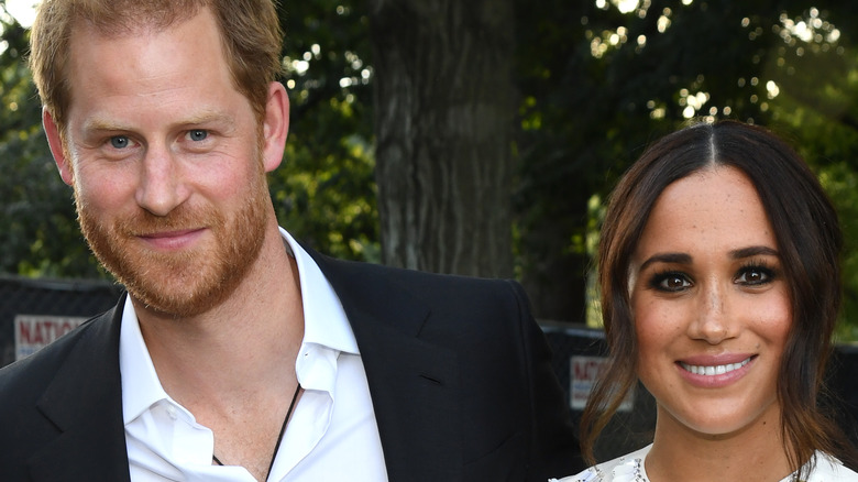Prince Harry and Meghan Markle smile for the camera.