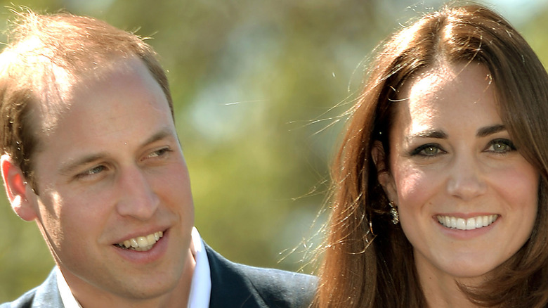 Prince William and Kate Middleton smiling at an event.