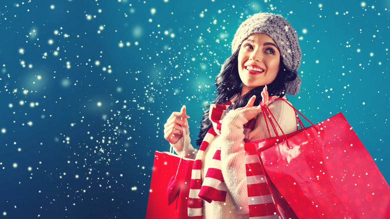 Woman dressed for the holidays carrying red shopping bags