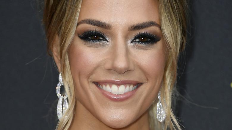 Jana Kramer smiling with dramatic eye makeup