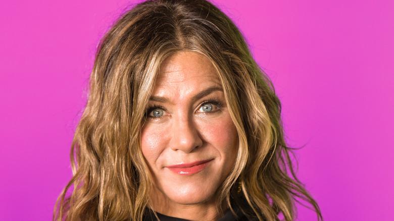 Jennifer Aniston smiling, pink background