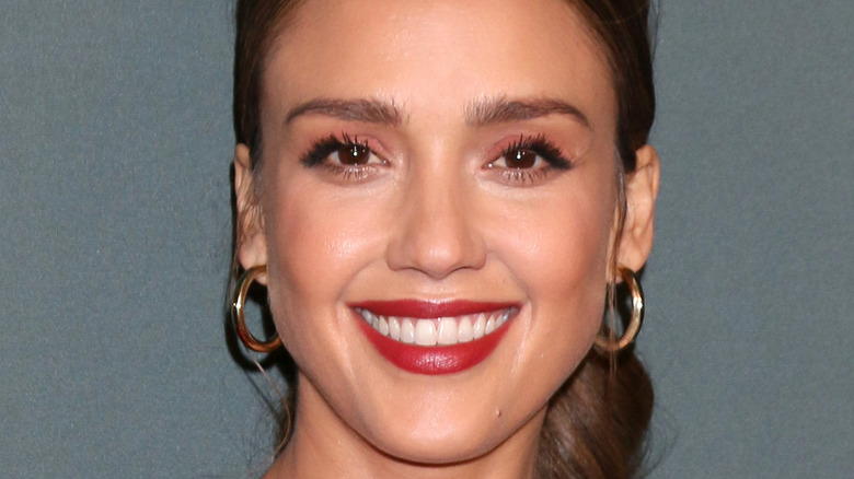 Jessica Alba smiles with red lipstick and hoop earrings.