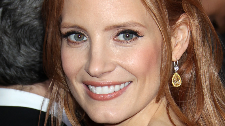 Jessica Chastain smiling over her shoulder for a picture