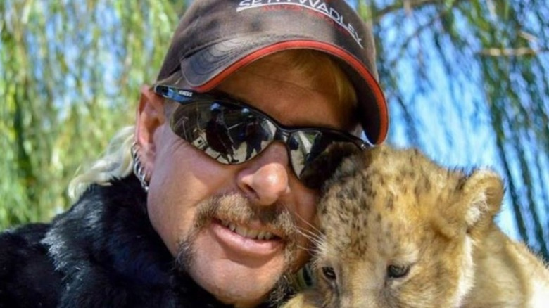 Joe Exotic poses with a baby tiger