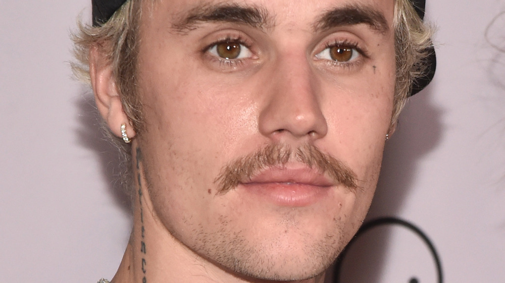 close up of Justin Bieber's face with neck tattoo