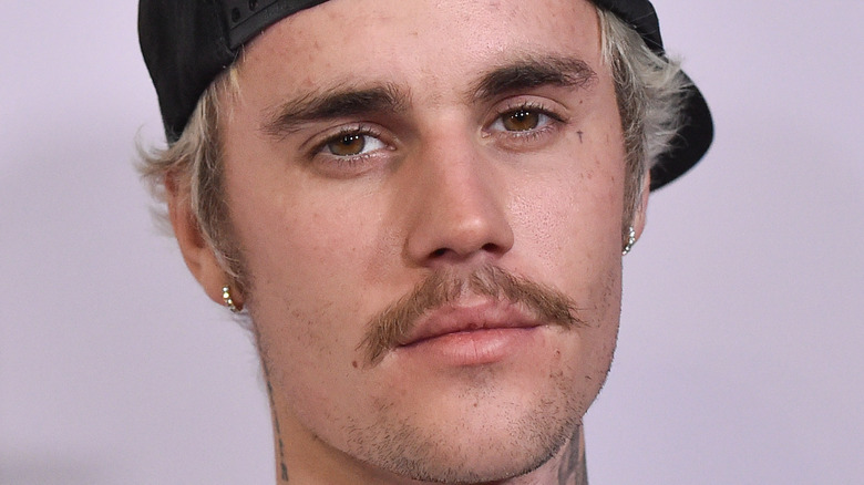 Justin Bieber with hat backwards and weird facial hair