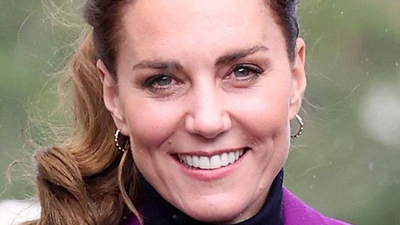 Kate Middleton smiles wearing purple coat.