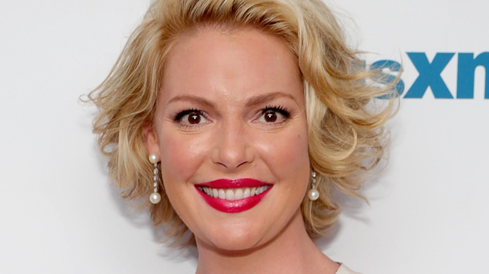 Katherine Heigl smiling in red lipstick and pearl drop earrings