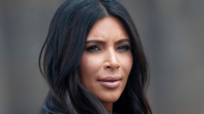 Kim Kardashian wears a brown coat.