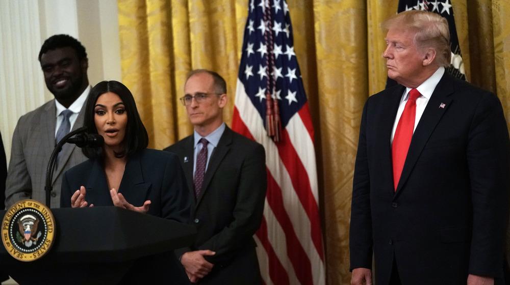 Kim Kardashian talking, Donald Trump watching