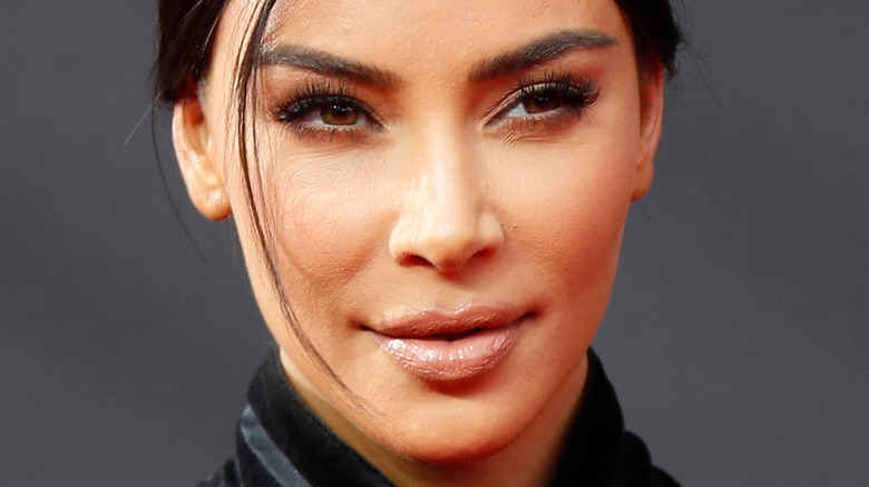 Kim Kardashian looking to the side with thoughtful expression