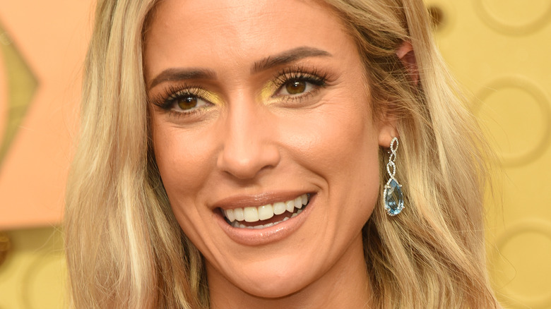 Kristin Cavallari smiles with her hair down and dangling earrings.
