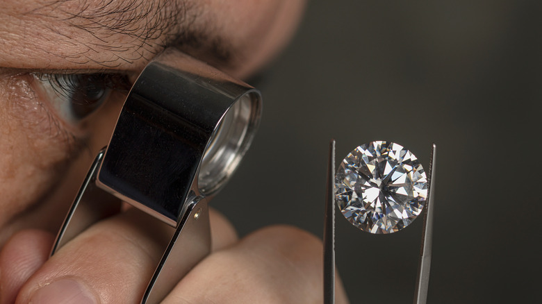 Man looking at a diamond with a magnifying glass