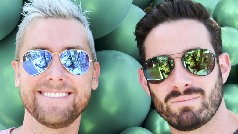 Lance Bass and Michael Turchin both wear sunglasses with balloon background