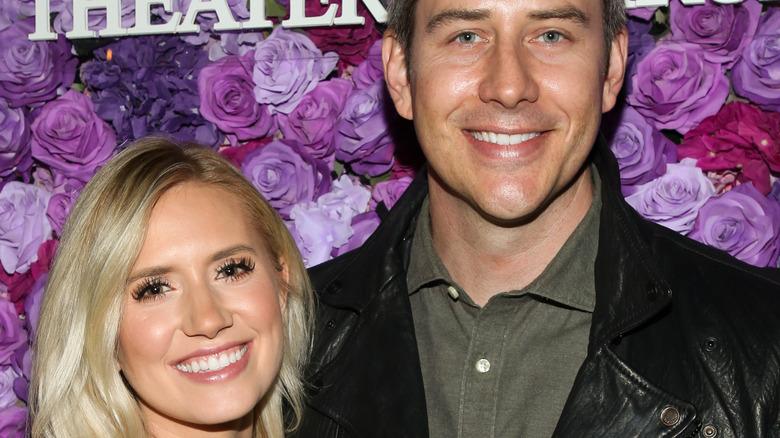 Arie Luyendyk and Lauren Burnham smile in front of rose backdrop