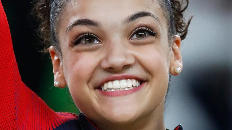 Laurie Hernandez waves while wearing Olympic medal