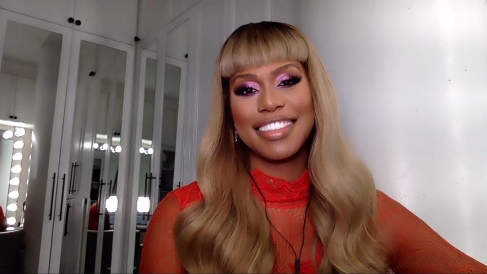 Laverne Cox smiling, blond hair, purple eyeshadow