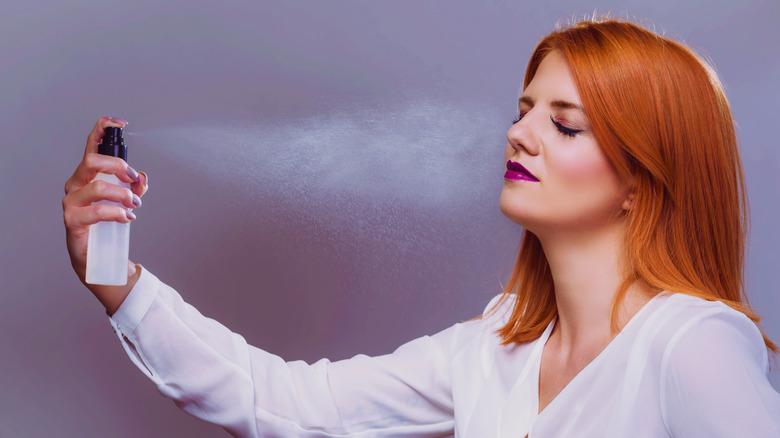 Woman applying makeup setting spray