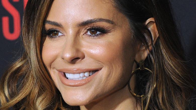 Maria Menounos smiling in gold hoop earrings