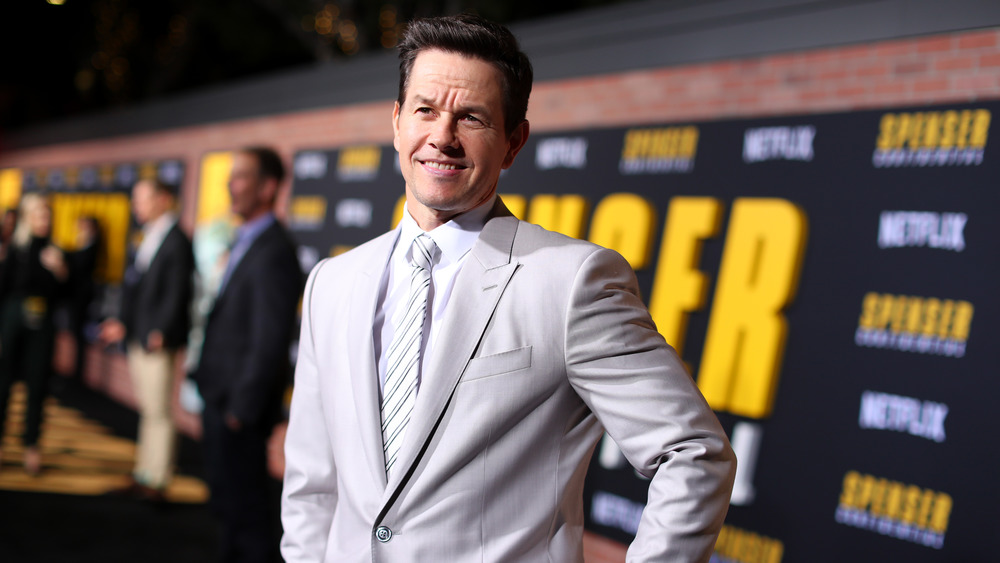 Mark Wahlberg posing at event in off-white suit