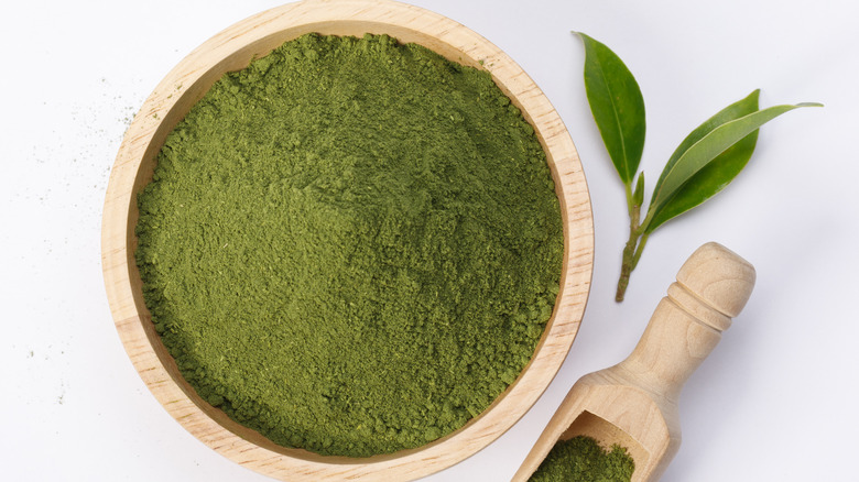 Green match powder in a wooden bowl against a white backdrop