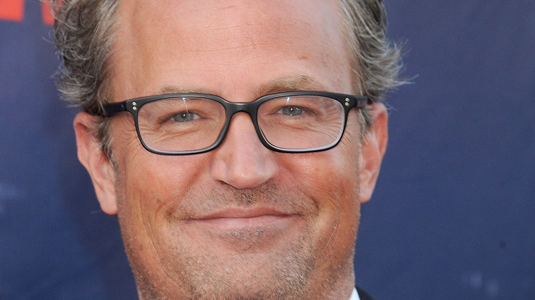 Matthew Perry smiles with glasses