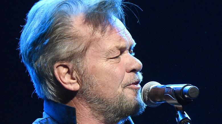 John Mellencamp singing while holding a guitar