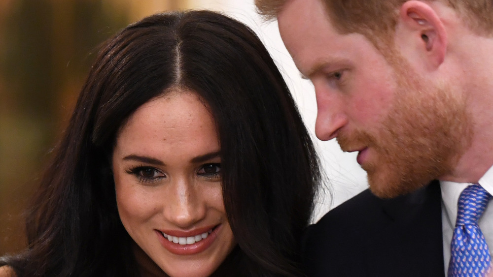 Meghan Markle smiling and Prince Harry in profile