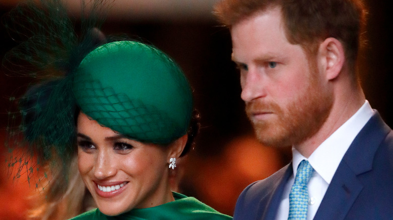 Meghan Markle smiling and Prince Harry straight-faced