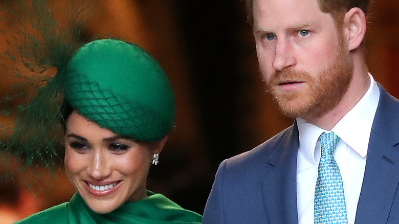 Meghan Markle smiling on Prince Harry's arm