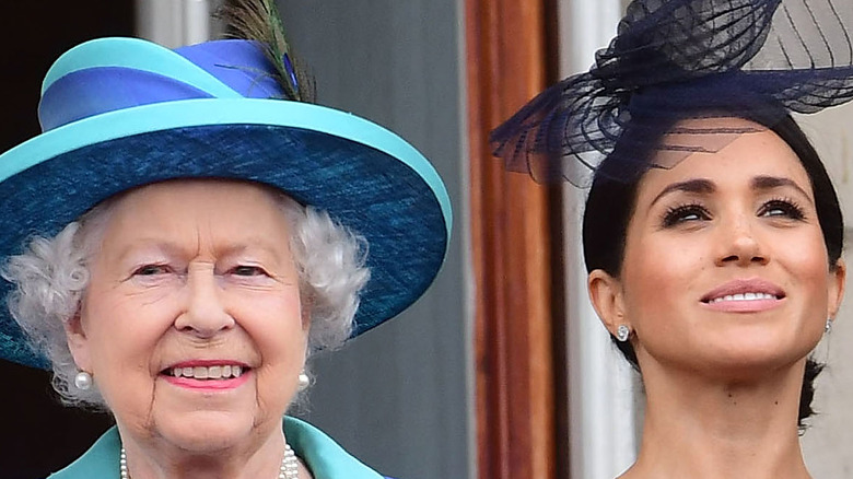 Queen Elizabeth and Meghan Markle smiling at event