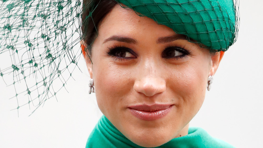 Meghan Markle looking off to the side and smiling