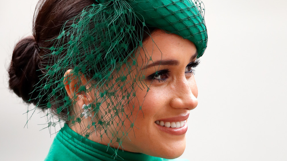 Meghan Markle smiles in a green hat