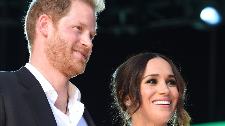 Meghan Markle and Harry posing on stage